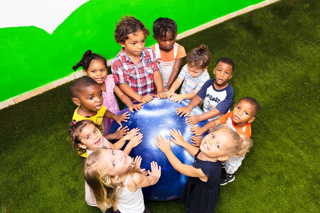 children holding their hands on blue ball